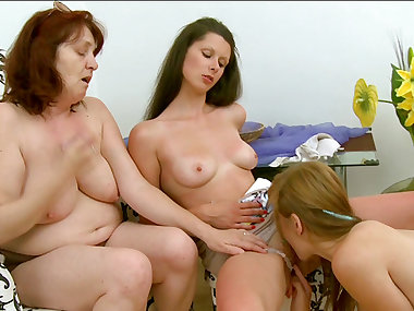 Two young girls and mature mom in the lesbian..
