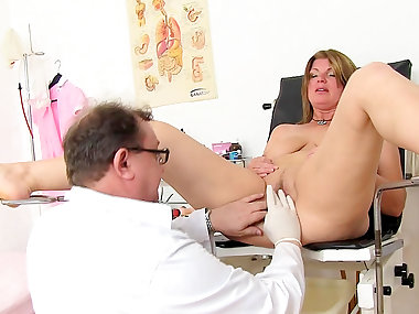 Mature is sitting in medical chair with spread..