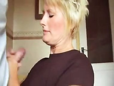 Short haired blonde mom drops to her knees and jerks off a