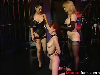 Redhead slave gets dominated by two mature dominas